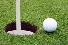 Golfball nahe Pin Stockbild