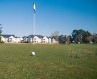 Golfball och flagga Arkivbild