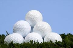 Golfball-Pyramide auf Gras gegen blauen Himmel Stockbild