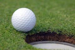 Golfball quasi nel foro Fotografie Stock