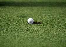 Golfball que cai no furo Foto de Stock Royalty Free