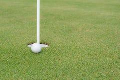 Golfball am Rand des Lochs lizenzfreies stockbild