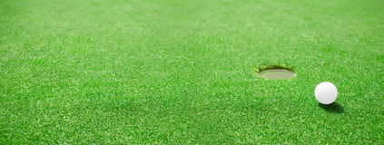 Golfball am Rand des Lochs stockfotos