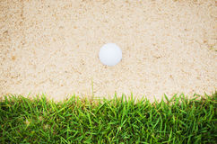 Golfball in sand Stock Image