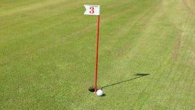 Golfball steigt in das Loch ein