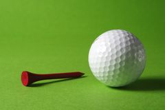 Golfball and tee. White golfball and tee on grass-green background royalty free stock photos