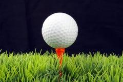 Golfball on tee. White golfball in orange tee, green fairway, isolated on black background Royalty Free Stock Photos