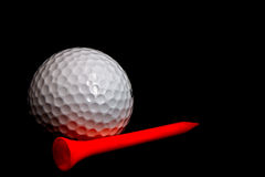 Golfball with tee. Isolated golfball with plastic tee in black background Stock Images