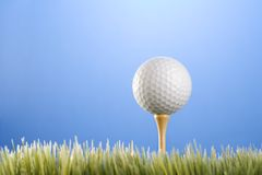 Golfball on a tee. Studio shot of a golfball on a tee in grass Stock Photos
