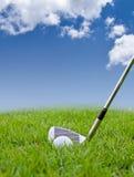 Golfball und Eisen auf hohem Gras Stockbild