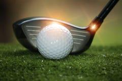 Golfball und Golfclub im schönen Golfplatz an Sonnenuntergang backg lizenzfreie stockfotografie