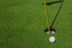 Golfball und Loch stockfotos