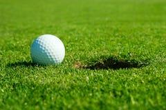 Golfball und Loch Stockbilder