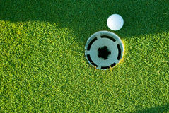Golfball und Loch Stockfoto