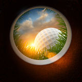 Golfball und Loch Stockbild