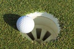 Golfball und Loch auf einem Feld Stockbild