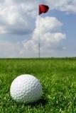 Golfball und Markierungsfahne Stockfotografie