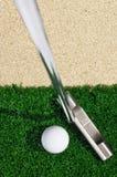 Golfball und Putter auf grünem Gras Stockfotos