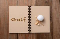 Golfball und T-Stücke auf offenem Notizbuch Stockbild