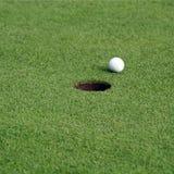 Golfball vor dem Loch Lizenzfreies Stockfoto