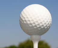 Golfball on white tee. Against blue sky Royalty Free Stock Images