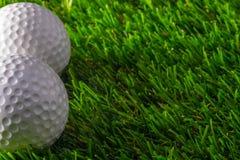 Golfball zwei auf Gras lizenzfreie stockbilder