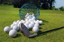 Golfballen die van mand op gras uitgieten royalty-vrije stock afbeeldingen