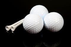 Golfballen en T-stukken op zwarte stock foto