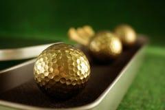Golfballs de oro en conjunto del regalo Foto de archivo