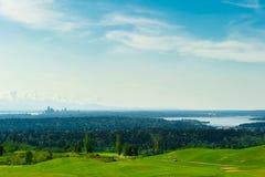 Golfbana med grönt gräs och Seattle som är i stadens centrum på Backgroen Royaltyfri Bild