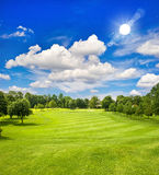 Golfbana och solig himmel för blått. grönt fältlandskap royaltyfri foto
