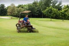 Golfbanaarbetaren mejar gräset royaltyfri bild