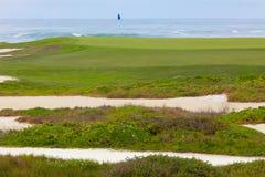 Golfbanan för havframdelen, sand bunkrar och gör grön att leda till hålet Royaltyfria Bilder