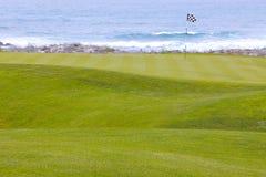 Golfbanan gör grön att leda till hålet vid havet Arkivfoto