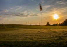 Golfbanan med två bollar nära sjunker i soluppgång royaltyfria foton