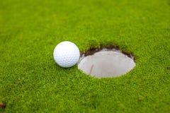 Golfboll går till hålet arkivfoton