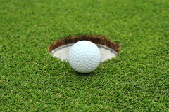 Golfboll går till kanthålet royaltyfria foton