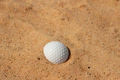 golfboll i sand på bunker Royaltyfri Foto