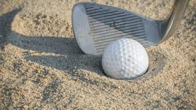 Golfboll i sandfälla med breddstegkilen arkivfoton