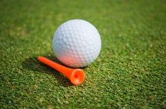 Golfboll med den orange utslagsplatsen på grönt gräs Arkivbild
