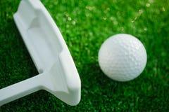 Golfboll med puttern på grön kurs Selektivt fokusera Arkivbilder