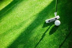 Golfboll med puttern på grön kurs Selektivt fokusera Royaltyfri Bild