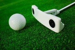 Golfboll med puttern på grön kurs Selektivt fokusera Royaltyfri Fotografi