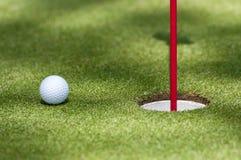 Golfboll in mot hålet Royaltyfri Bild