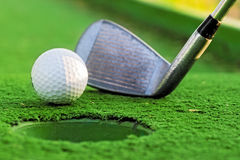 Golfboll nära hålet arkivfoto