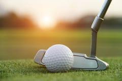 Golfboll och golfklubb i härlig golfbana på solnedgångbakgrund royaltyfri bild