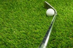 Golfboll och golfklubb på gräs royaltyfri fotografi