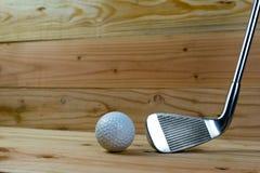 Golfboll och golfklubb på trägolv arkivfoto