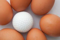 Golfboll och grupp av nya ägg Arkivfoto