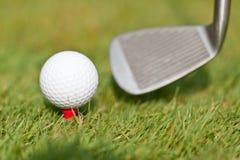 Golfboll och järn på grönt gräs specificerar utomhus- makrosommar Arkivfoton